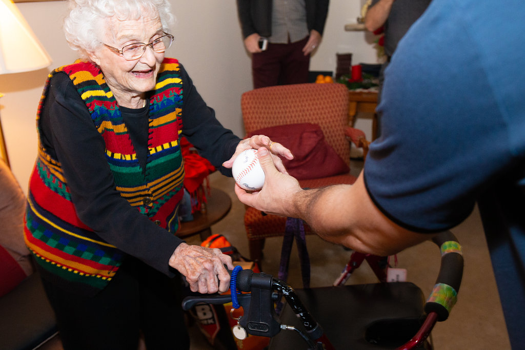 man giving elderly woman a baseball