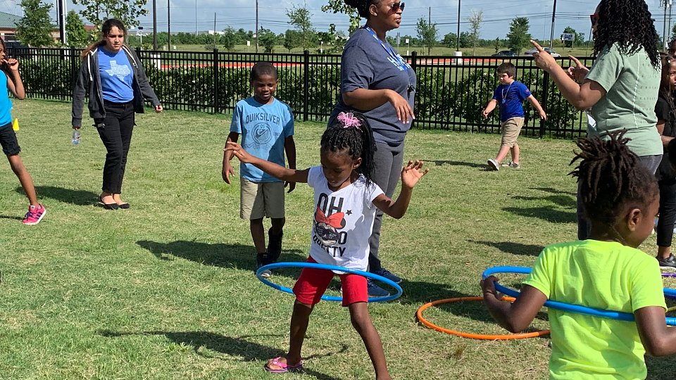 children from buckner family hope center houston play field games