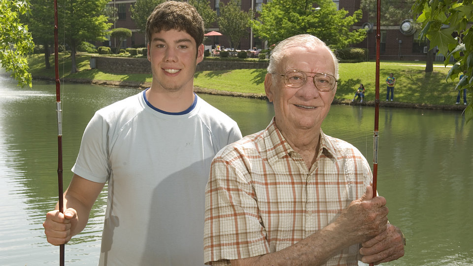 happy senior citizen fishing with grandson