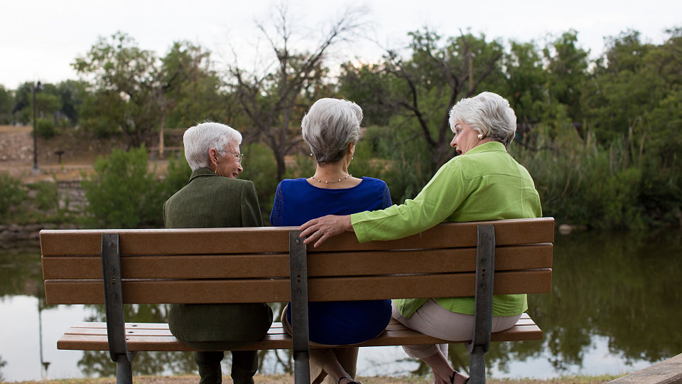 senior friends chatting on a park bench