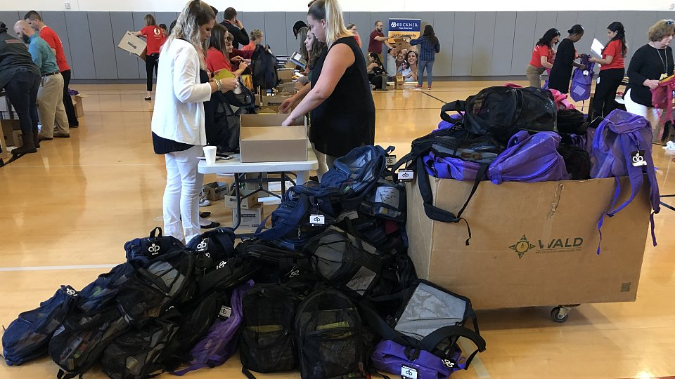 halliburton employees filled backpacks to give to children served by buckner