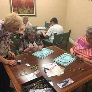 Making beaded jewelry at a craft class at Buckner Villas.
