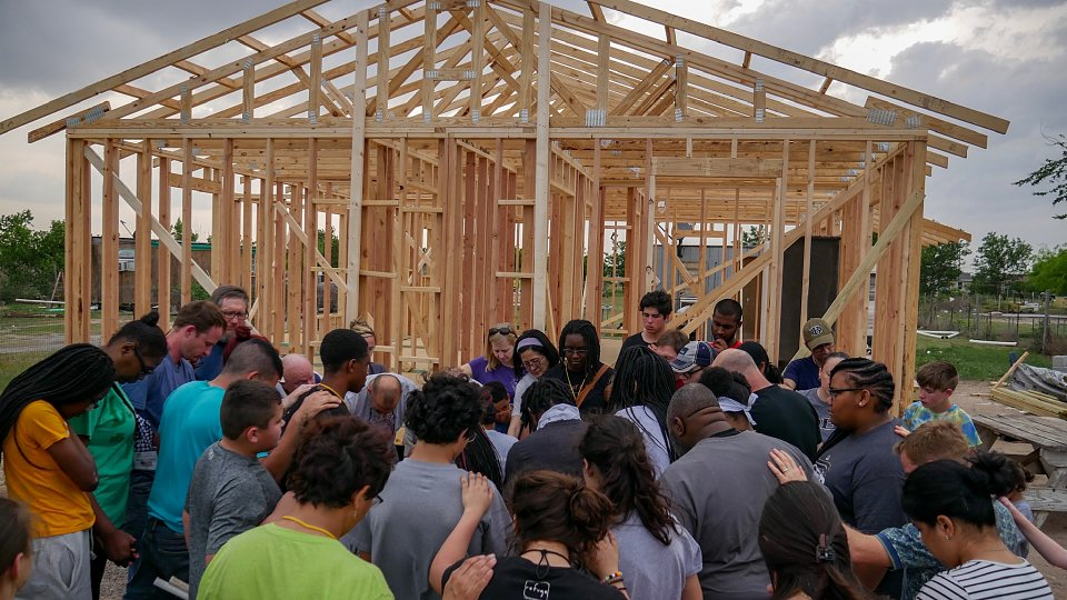 volunteers prays with family who is receiving a new home